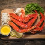 alaskan-king-crab-legs-with-butter-lemons-wooden-space_192913-32